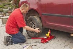 Equipe a mudança do pneumático puncionado em seu carro que afrouxa as porcas com uma chave inglesa da roda antes de levantar acim fotos de stock royalty free