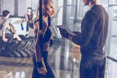 Equipe a mulher desportivo de ajuda que exercita com equipamento do gym do trx Imagens de Stock Royalty Free