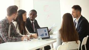 equipe Multi-étnica do negócio que compartilha das ideias que sentam-se na tabela do escritório da conferência vídeos de arquivo