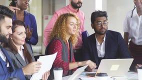 A equipe multi-étnica nova do trabalho troca as ideias que recolhem em torno dos laptop filme