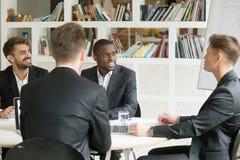 Equipe multi-étnico dos colegas de trabalho masculinos que discutem os planos incorporados du Fotos de Stock