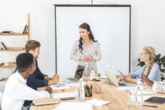 equipe multicultural do negócio que discute a estratégia e ideias novas na reunião imagem de stock