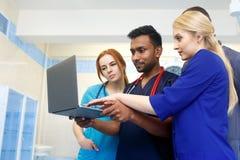 Equipe multirracial dos doutores novos que trabalham no laptop no escritório médico fotos de stock royalty free