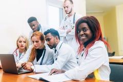 Equipe multirracial dos doutores novos que trabalham no laptop no escritório médico fotos de stock