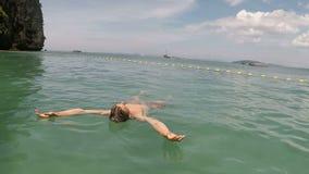 Equipe a natação sobre para trás na câmera pov da ação do mar do indivíduo novo que encontra-se na água na praia bonita filme