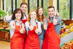 Equipe no supermercado que mantém os polegares imagem de stock