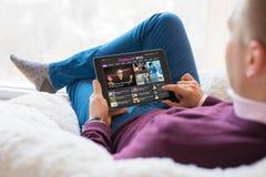 Equipe a notícia da tecnologia da leitura na tabuleta ao sentar-se em casa imagens de stock royalty free