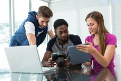 Equipe nova criativa do negócio que olha a tabuleta digital Imagem de Stock