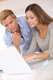 Equipe nova do negócio que senta-se na mesa com portátil imagem de stock royalty free