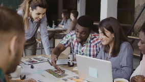Equipe nova do negócio que trabalha no escritório Grupo de pessoas da raça misturada que discute a concepção arquitetónica para a filme