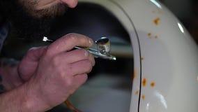 Equipe o adulto farpado na pintura preta do tampão com o aerógrafo na asa do carro na garagem feita sob encomenda video estoque