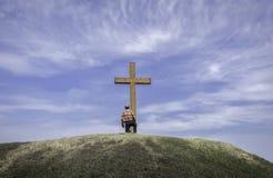 Equipe o ajoelhamento por uma cruz em um monte nas horas de verão imagens de stock royalty free