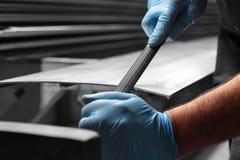 Equipe o arquivamento que deburring um painel do metal com um arquivo fotos de stock