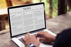 Equipe o artigo noticioso da leitura no portátil/tela de computador fotos de stock royalty free