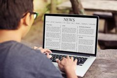 Equipe o artigo noticioso da leitura no portátil/tela de computador foto de stock