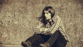 Equipe o assento de cabelos compridos apenas triste na parede do grunge fotografia de stock royalty free