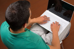 Equipe o assento e o trabalho usando o portátil branco como visto de cima com das mãos que datilografam no teclado Foto de Stock