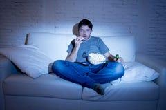Equipe o assento em casa do sofá no filme ou no esporte de observação da sala de visitas na tevê que come a pipoca e que bebe a c fotografia de stock