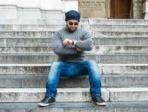 Equipe o assento em escadas e a vista de seu relógio Imagem de Stock