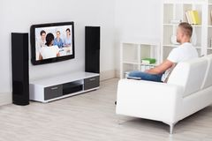 Equipe o assento em um sofá em sua televisão de observação da sala de visitas Imagens de Stock Royalty Free