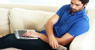 Equipe o assento em um sofá usando seu portátil e chamando o telefone filme