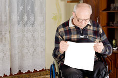 Equipe o assento em uma cadeira de rodas que lê o jornal Imagens de Stock