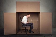 Equipe o assento em uma caixa que trabalha no portátil fotografia de stock royalty free