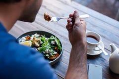 Equipe o assento em uma tabela dos restaurantes que come a salada deliciosa imagens de stock