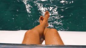 Equipe o assento na curva do barco com pés e pés ao mar filme