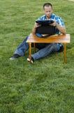 Equipe o assento na grama fora na frente de uma tabela Fotografia de Stock Royalty Free