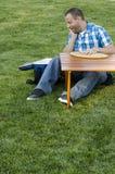 Equipe o assento na grama fora na frente de uma tabela com um refrigerador Fotografia de Stock Royalty Free