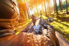 Equipe o assento na motocicleta na estrada de floresta fotografia de stock
