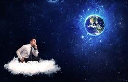 Equipe o assento na nuvem que olha a terra do planeta Fotos de Stock Royalty Free