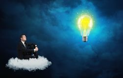 Equipe o assento na nuvem que olha uma ampola Foto de Stock