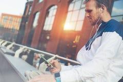 Equipe o assento na rua com o telefone celular e os relógios espertos, datilografando a mensagem fotos de stock royalty free