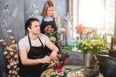 Equipe o assento na tabela e na mulher que guardam a flor perto dele Fotografia de Stock Royalty Free