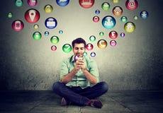 Equipe o assento no assoalho usando os ícones da aplicação do smartphone que voam acima Fotos de Stock