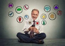 Equipe o assento no assoalho usando texting em aplicações sociais dos meios da Web da consultação do smartphone Fotos de Stock