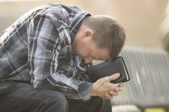 Equipe o assento no banco e rezar com a Bíblia imagens de stock royalty free