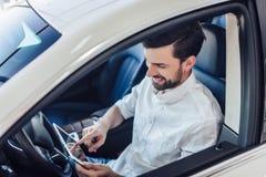 Equipe o assento no carro usando a tabuleta digital imagens de stock royalty free