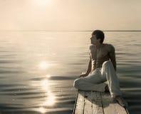 Equipe o assento no molhe de madeira pequeno no dia ensolarado do verão fotografia de stock