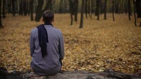 Equipe o assento no parque sozinho, tons cinzentos expressam a depressão, tristeza, melancolia imagem de stock
