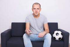 Equipe o assento no sofá com bola de futebol e a tevê de observação em casa Fotografia de Stock Royalty Free