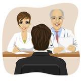 Equipe o assento oposto ao doutor maduro com o assistente que senta-se em uma mesa de escritório Fotografia de Stock Royalty Free