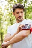 Equipe o atleta que está e que usa o smartphone no handband na floresta Fotografia de Stock