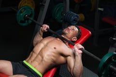 Equipe o atleta que exercita no gym com um barbo imagem de stock