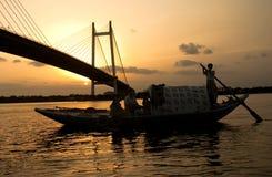 Equipe o barco de navigação no por do sol perto de uma ponte Foto de Stock Royalty Free