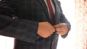 Equipe o botão acima de seus botões em seu revestimento, close-up o homem de negócios põe sobre um casaco azul em uma gaiola o tr video estoque