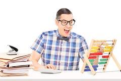 Equipe o cálculo em um ábaco assentado em uma tabela Fotografia de Stock