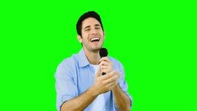 Equipe o canto no microfone com emoção na tela verde vídeos de arquivo